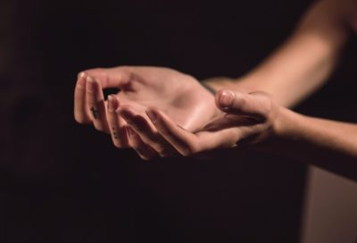 Woman's hands, reflecting on trauma being stored in the body.