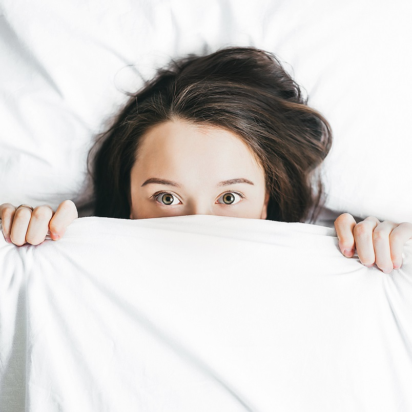 Woman lying in bed worrying how anxiety affects sleep,.