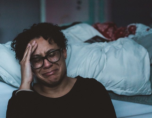Woman crying as she worries about how it feels when your anxiety is debilitating.
